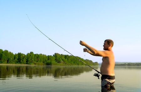 fisherman fishing in a calm river in the morning. Man in fishing gear stending in a river and throws a fishing pole Stock Photo