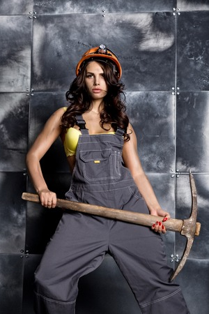 Beautiful sexy worker with a pickaxe. Seductive and beautiful woman miner on a steel background 免版税图像
