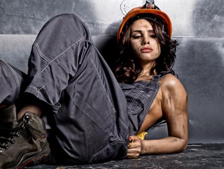 鋼の背景に床に座って懐中電灯とオレンジ色のヘルメットで美しい疲れセクシーな鉱山労働者