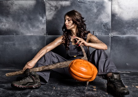 Beautiful tired sexy miner worker in orange helmet with flashlight sitting on a floor on steel background. woman holding pickaxe Stock Photo