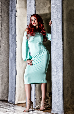 sexy beautiful redhead young woman with big boobs in a turquoise dress on a old gray wall background