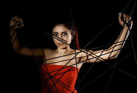 beautiful young woman in red dress entangled in a rope cobweb on a black background Imagens