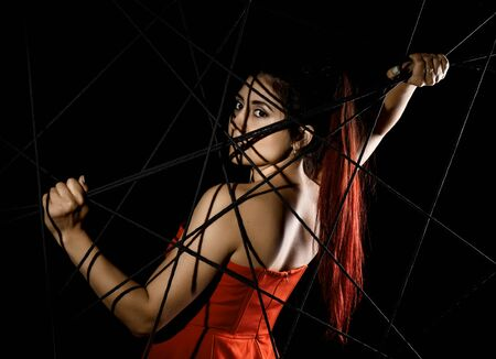 beautiful young woman in red dress entangled in a rope cobweb on a black background Stock Photo