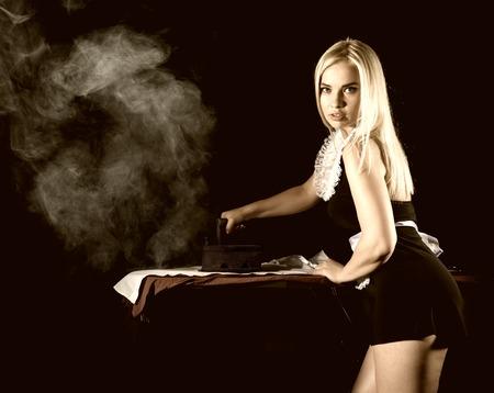 セクシーな金髪女性家政婦スーツの古い鉄と白いシャツをアイロンします。暗い背景にレトロなスタイル