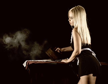 sexy blonde woman in housekeeper suit, ironing white shirt with old iron. retro style on a dark background