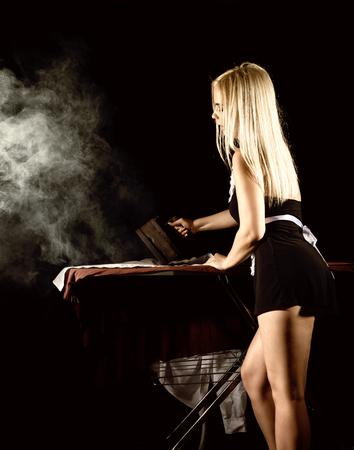 Sexy blonde Frau in Haushälterin Anzug, Bügeln weißes Hemd mit altem Eisen. Retro-Stil auf einem dunklen Hintergrund