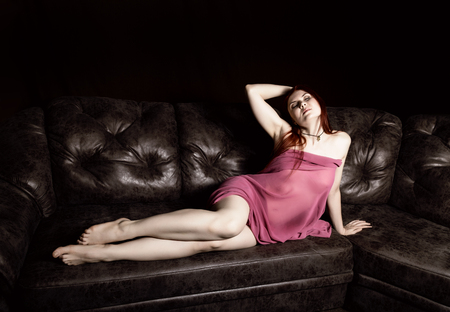 redhead beautiful naked young woman in a light transparent cape lying on a black leather sofa on a black background 免版税图像