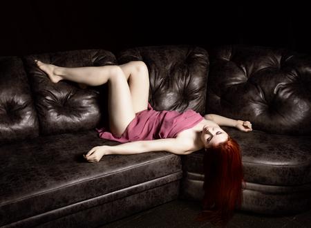 roodharige mooie naakte jonge vrouw in een lichte transparante cape liggend op een zwarte lederen sofa op een zwarte achtergrond Stockfoto