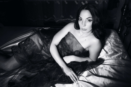 adult sex: Veiled sexy brunette beauty lies on a bed. black and white