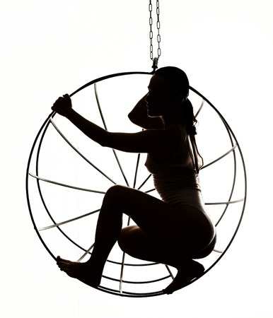 Silhouette of a sexy woman on a metal cage, black and white