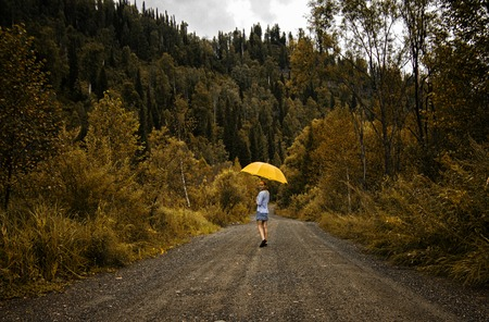 back alley: Beautiful woman hold yellow umbrella and walks on a country road under rain