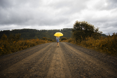 Beautiful woman hold yellow umbrella and walks on a country road under rain