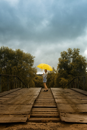 back alley: Beautiful woman hold yellow umbrella and walking on a old bridge in the countryside under rain