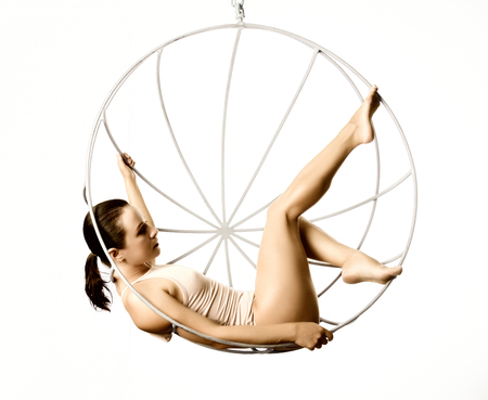 sexy woman in a beige swimsuit on a metal swing on a white background Stock Photo