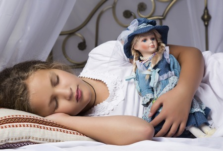 beautiful little girl sleep in a bed and hug her baby doll.