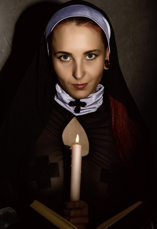 Beautiful nun with a candle reading the Bible. religious concept Stock Photo