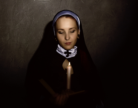 Beautiful nun with a candle reading the Bible. religious concept.