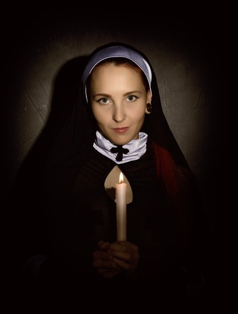 Beautiful nun with a candle on a dark background. religious concept Stock Photo