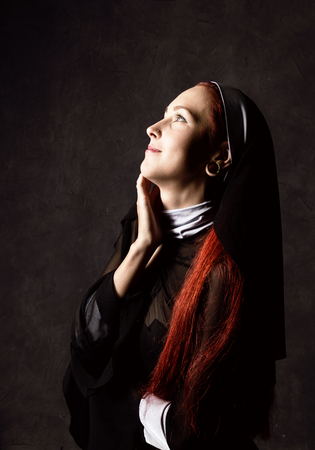 Beautiful sexy catholic nun posing on a dark background. religious concept.