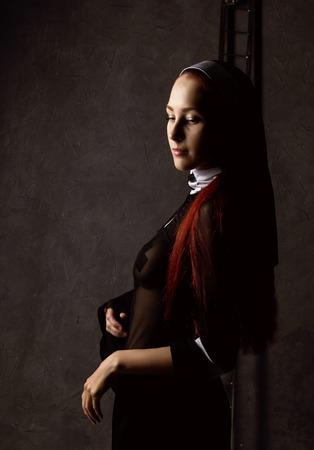 Beautiful sexy catholic nun posing on a dark background. religious concept Stock Photo