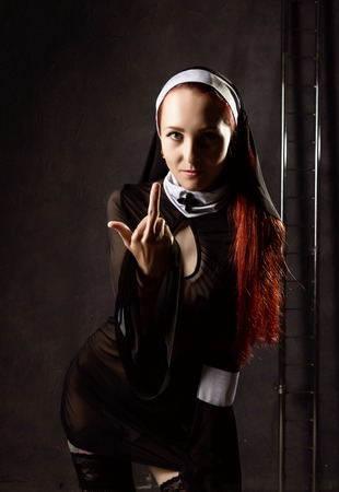 Cheeky beautiful sexy catholic nun shows middle finger. religious concept