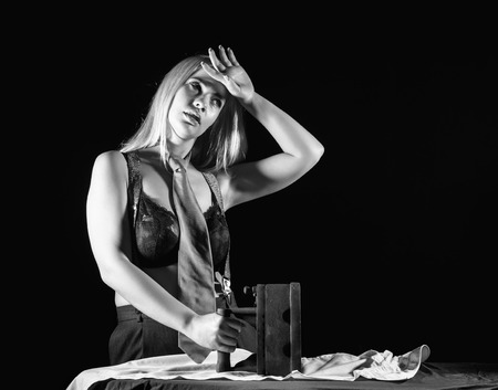 sexy blonde woman in mens pants and a bra, ironing white shirt with old iron. retro style, black and white Stock Photo