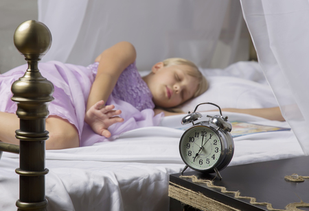 Alarm clock standing on bedside table. Wake up of an asleep young girl stopping alarm clock on a bed in the morning