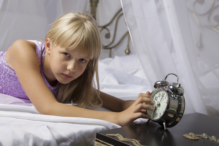 hate: Early awakening. Wake up of an asleep young girl stopping alarm clock on a bed in the morning