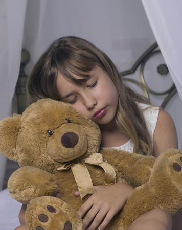 Early awakening. Alarm clock standing on bedside table. Wake up of an asleep young girl holding teddy bear in bed on a background
