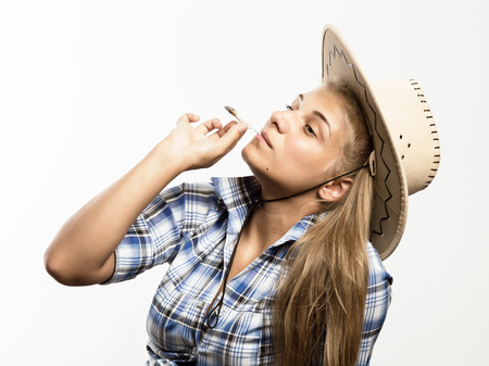 Young beautiful woman in cowboy hat and checkered shirt smoking marijuana on a white background.