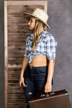 cowboy girl or pretty woman in stylish hat and blue plaid shirt holding gun and old suitcase Stock Photo