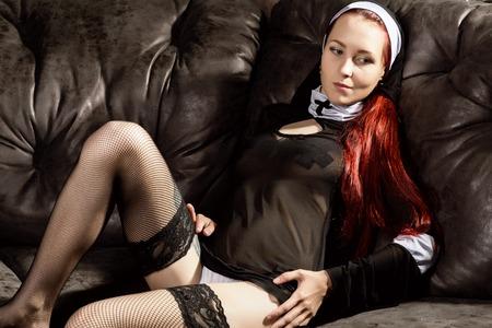 美しいセクシーなカトリックの修道女黒革ソファーでポーズします。腐った宗教概念
