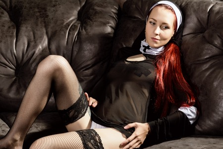 Beautiful sexy catholic nun posing on a black leather sofa. Rotten religion concept