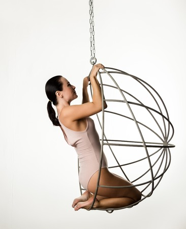 sexy woman in a beige swimsuit on a metal cage on a white background