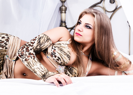 Beautiful girl in the Arabian national bright dress with oriental makeup is lies on a bed