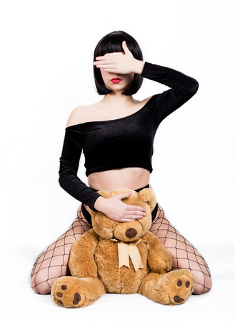 eccentric girl with teddy bear closed her eyes with her palm on white background. brunette woman in black panties and net pantyhose