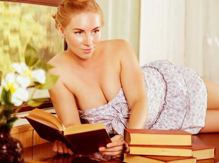 nightwear: young woman reads a book lying on a desk in front of a window. old style, lolita concept.