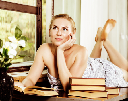 windows: young woman reads a book lying on a desk in front of a window. old style, lolita concept.