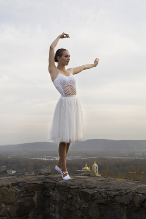 sipario chiuso: young ballerina in white dress and satin ballet shoes posing on the edge of old fortress wall on a grey sky background.