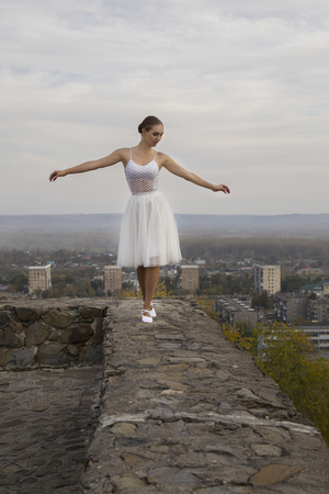 young ballerina in white dress and satin ballet shoes posing on the edge of old fortress wall on a grey sky background.