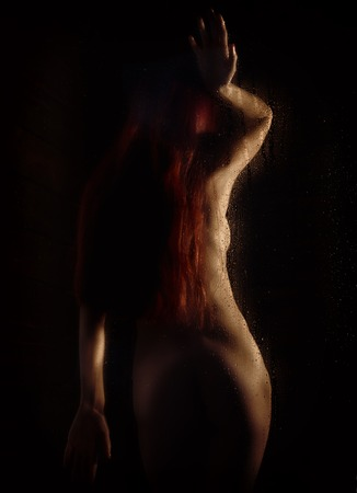 redhead naked young woman with water droplets on a body on a dark background.