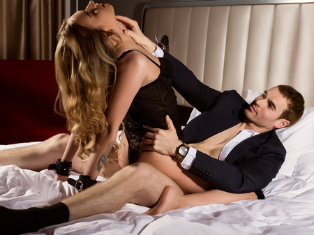 undressed sensual woman in black lace erotic lingerie sitting on a handsame guy. intimate moments of a young couple