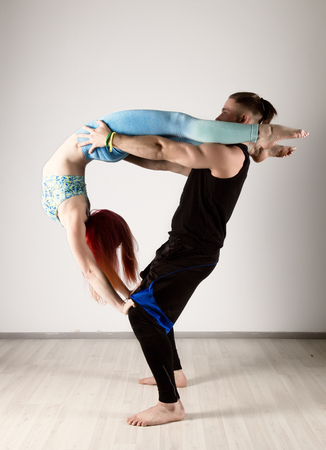guy and young woman doing strength exercises in yoga assanes. Acroyoga concept
