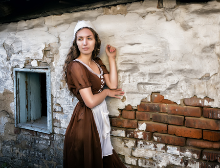 pensive young woman in a rustic dress standing near old brick wall in old house feel lonely. Cinderella style