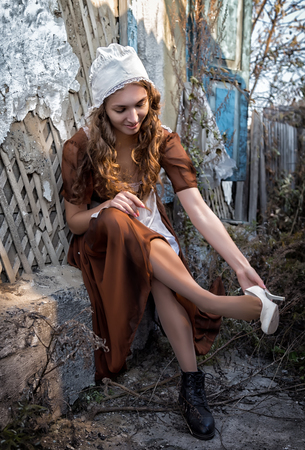 sad woman in a rustic dress sitting near old brick wall in old house and trying to dress a white shoe. Cinderella style Stock Photo