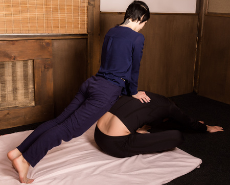 beautiful girl doing thai back massage in spa saloon
