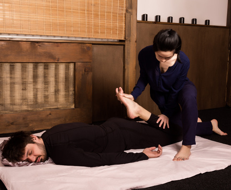 Foot massage in thai studio. Professional therapist giving traditional Thai massage