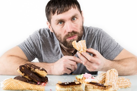 bearded man eating cupcakes with pleasure after a diet. harmful but delicious food