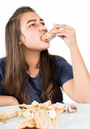 Young woman eating cupcakes with pleasure after a diet