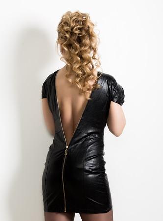 Bella giovane donna che indossa abito corto in pelle nera con schiena nuda su uno sfondo chiaro
